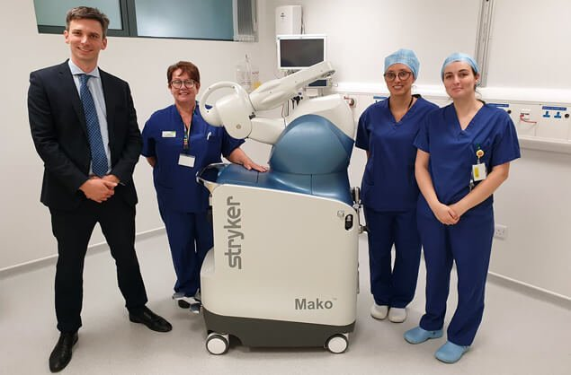 Damian Clark is a Bristol knee surgeon who specialises in treating knee pain and this picture shows him and three nurses standing in theatre with the robotic-assisted knee replacement technology that he uses for certain knee surgeries