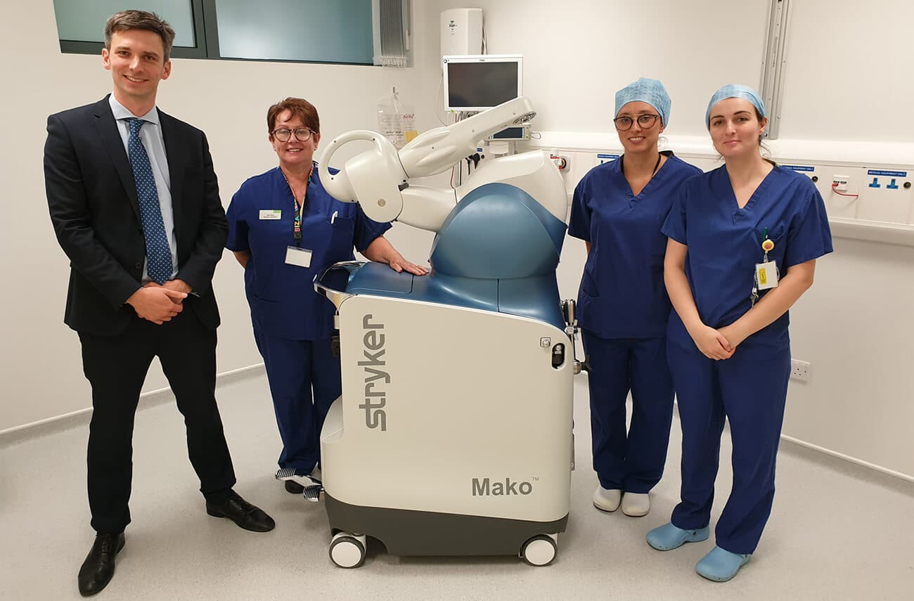Damian Clark a Bristol knee surgeon and 3 nurses standing in theatre with the robotic-assisted knee replacement technology