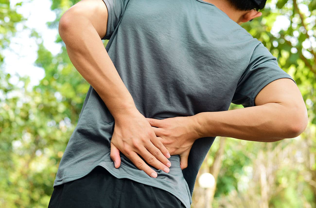 Picture of an athletic looking man in the woods holding his back pain with both hands