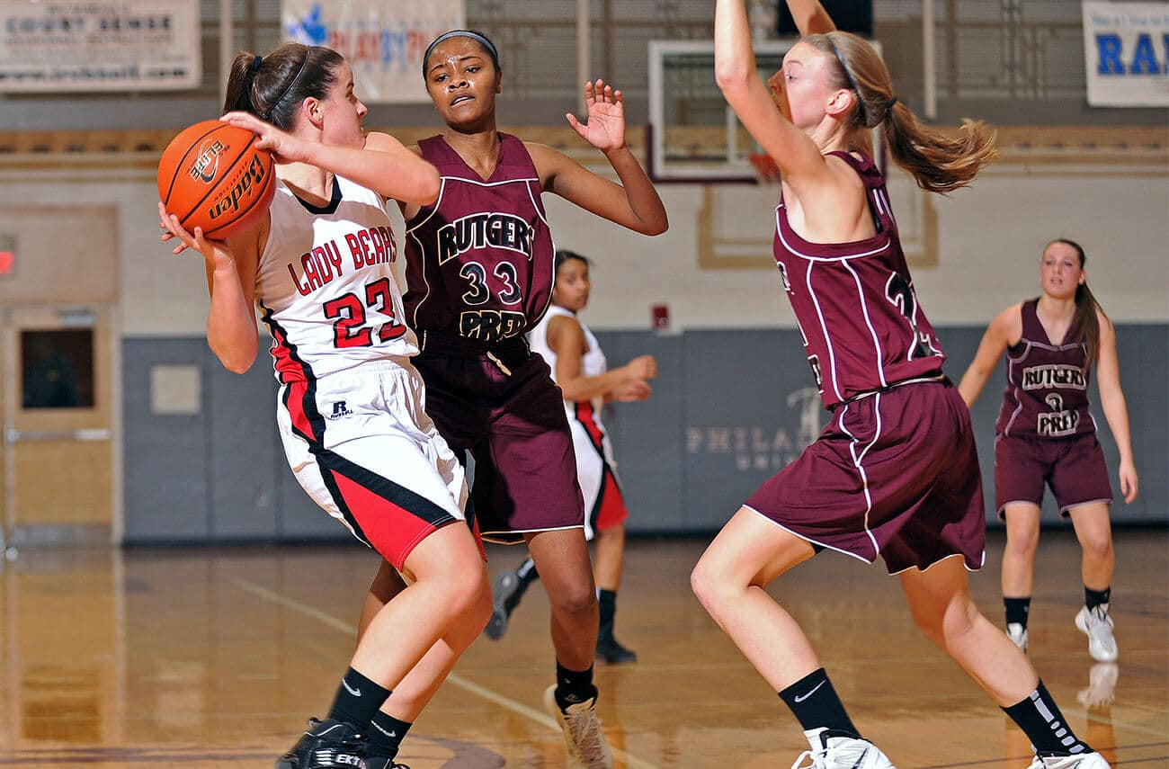 female teens playing in a basketball match which carries a higher risk of causing patellofemoral pain