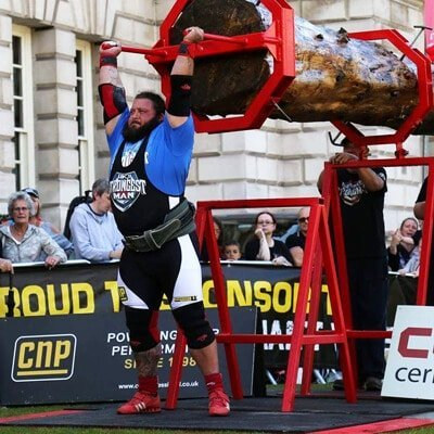 picture of postoperative UK strongman contender in competition weight-lifting a tree trunk after a successful ACL knee injury surgery and rehabilitation programme